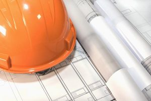 construction project management represented by architectural plans, project drawings, blueprint rolls and a hard hat