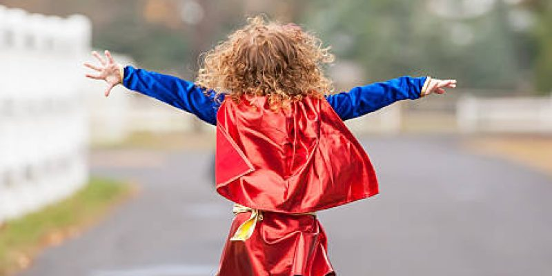 Rear view of a little girl running outside wearing a superhero costume. Her arms are out to each side as she pretends to fly like a superhero.