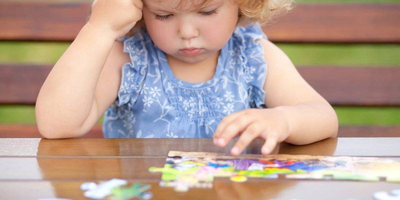 blonde unhappy toddler girl, solving puzzle on a table, hard difficult task. Early education and developement. Little genius concept. Emotional. (blonde unhappy toddler girl, solving puzzle on a table, hard difficult task. Early education and develope